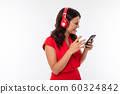 attractive brunette girl in a red dress listens to music on headphones with a phone in her hands on 60324842