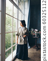 beautiful Asian woman with a hairstyle in Japanese style and a kimono at the window on the background of the home interior 60325112