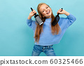 beautiful european girl combing her hair on a light blue background 60325466