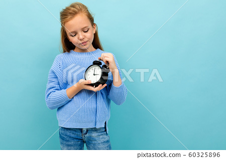 European disgruntled girl looks at the time of the alarm on a light blue background 60325896