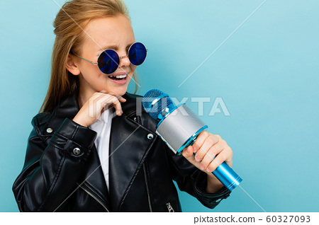 attractive european girl in a leather jacket in sunglasses singing with a microphone on a light blue 60327093