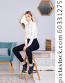 Full length portrait of young girl sitting on 60331275