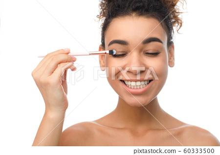 Happy black woman applying eyeshadows with brush 60333500