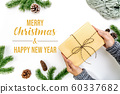 Christmas winter composition. Woman hand hold christmas gift box with pine cones, fir branches 60337682