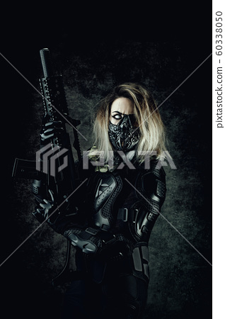 Young one-eyed Cyborg, wearing a mask, in combat armor, holding a machine gun in his hand 60338050