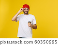 Man on isolated vibrant yellow color taking a coffee in takeaway paper cup and smiling because he will start the day well. 60350995