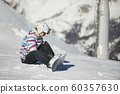 Snowboarder sitting in the snlow 60357630