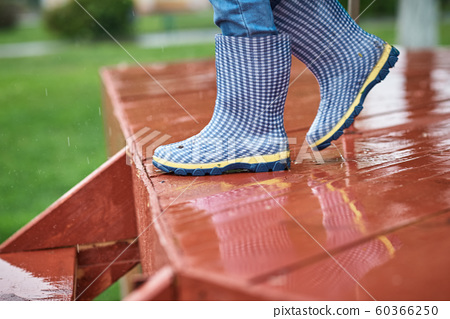 Boy in blue rubber boots down wet slippery stairs 60366250