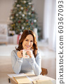 Pretty yuoung woman with cup in her hands spending christmas at home 60367093