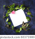 Invitation or greeting card square design template with a flatlay wreath of leaves and flowers, shot from above with a place for text. Ivy and rose frame on a dark background 60373980
