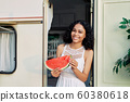 Happy young african american woman is holding slice of watermelon 60380618