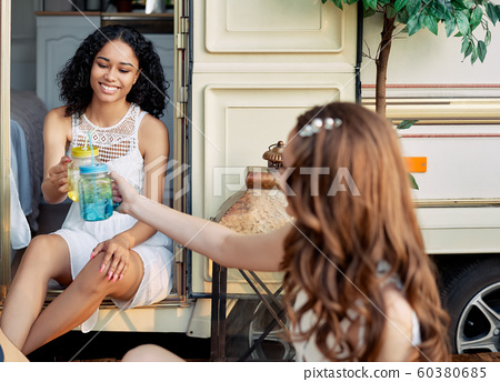Cheers. Two beautiful girls cheering with cocktails during a picnic outdoors 60380685