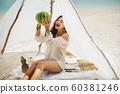 Woman on the Beach Eating Watermelon 60381246