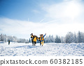 Group of young friends on a walk outdoors in snow in winter forest, running. 60382185