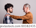 Portrait of a cheerful senior father and young son in a studio. 60382435