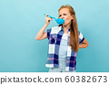 smiling european girl tastes with a spoon in her hands on a light blue wall 60382673
