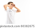 cute boy with bangs in a white t-shirt holds his hands like binoculars on a white background with 60382675