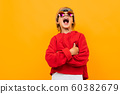blond boy with a bandana on his head in a red sweater and glasses posing on an orange background 60382679