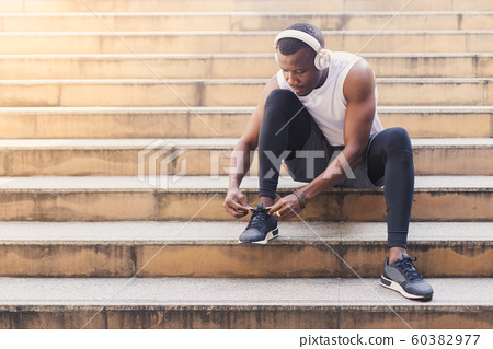 African American man tied up shoes on stairs after running exercised. 60382977