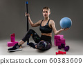Sport caucasian girl with slim figure do exercises with various sports equipment isolated on black 60383609