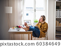 Young woman sitting at the table indoors at home, reading a book. 60384649