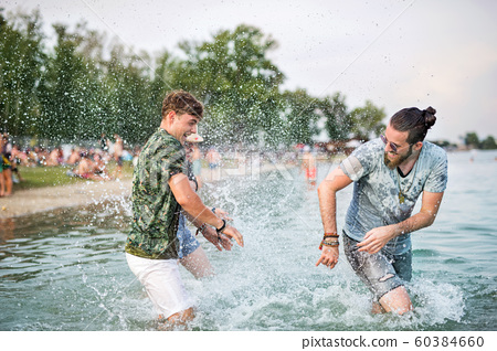 Young men friends having fun at summer festival, standing in lake. 60384660