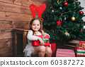 Happy little smiling girl with christmas gift box 60387272