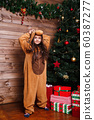 Funny little girl in pajamas jumping and having fun near Christmas tree 60387277