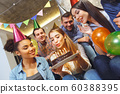 Group of friends having party indoors fun together girl blowing candles 60388395