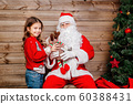 Santa Claus giving a present to a little cute girl near Christmas tree at home 60388431