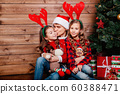 Smiling father in santa hat and daughter hugging and holding gift box near Christmas tree at home. 60388471
