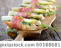 Delicious morsels with white asparagus on rocket leaves wrapped with Italian prosciutto 60388681