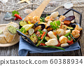 Fried mixed seafood and fresh colorful vegetables served in an iron frying pan 60388934