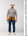 Young technician with toolbelt on his waist standing in front of camera 60389649