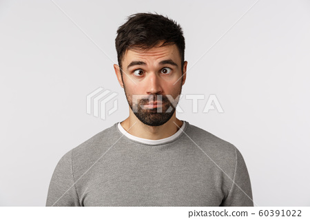 Emotions, people concept. Funny and goofy cute bearded guy making crazy eyes, squinting and grimacing, pouting, standing playful, trying make friends laugh, standing white background 60391022
