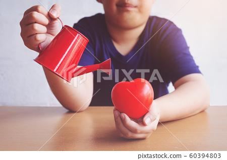 Boy watering heart red. valentine 60394803
