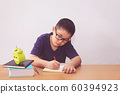Asian boy writeing a book on table 60394923