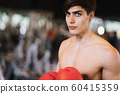 Portrait. Caucasian athlete standing while wear boxing glove color red  on blurred  background 60415359