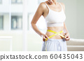 Young woman measuring her waistline 60435043