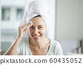 Young woman cleaning her face using a cotton disc. 60435052