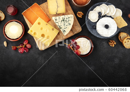 Cheese assortment with copy space, a flat lay overhead shot on a dark background with a place for text 60442068