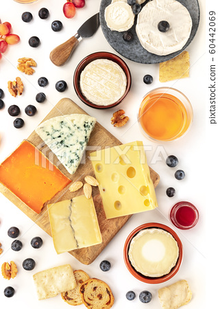 Cheese board, a flat lay overhead shot on a white background. Blue cheese, red Leicester, Emmental, goat cheese, Brie and others with wine, fruits, nuts and almonds 60442069