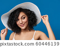 Playful woman wearing summer straw hat with wide brims 60446139