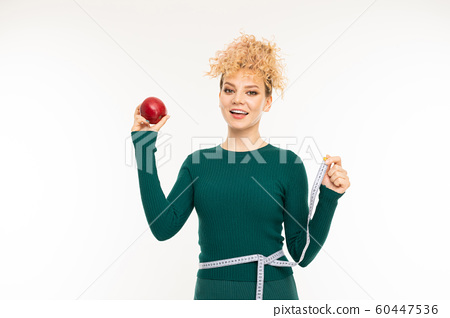 attractive curly blond girl with a good figure holds an red apple in his hand on a white wall 60447536