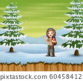 Explorer girl with backpack standing in winter 60458412
