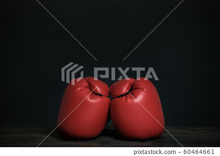 Pair of red boxing gloves on a black background. 60464661