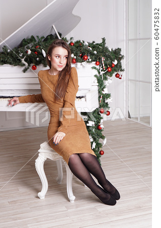Beautiful girl with long hair near a white piano with Christmas decoration 60475832