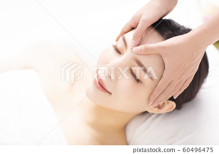 closed young woman face and head massage in spa 60496475