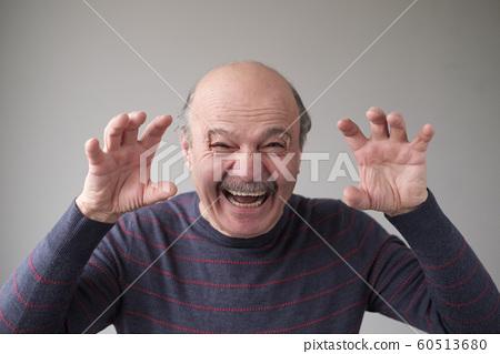 Senior hispanic man with creepy face grimacing to scare you 60513680