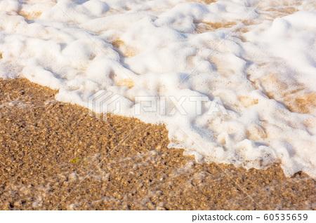 sea waves splash foam on the sunny beach 60535659